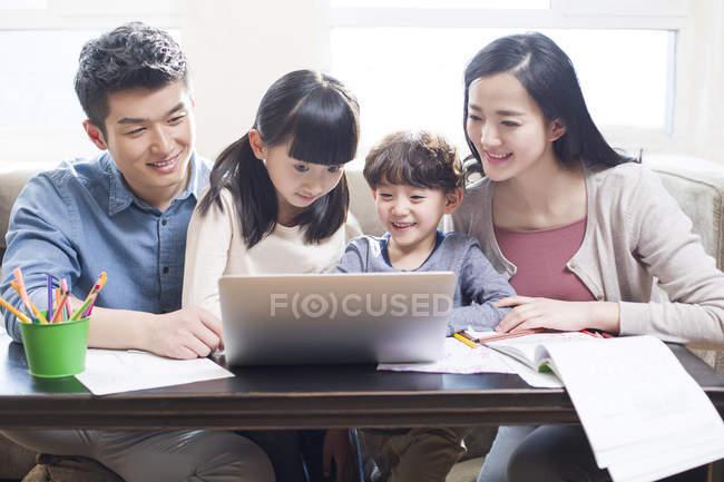 Chinesische Eltern mit Kindern benutzen Laptop im Wohnzimmer — Stockfoto