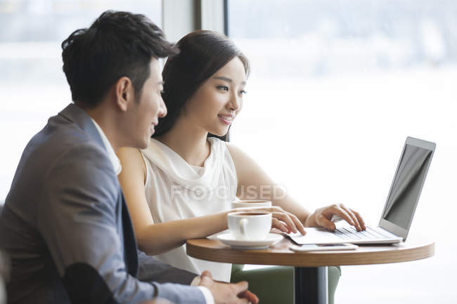 Chinese businesswoman and businessman working with laptop in cafe — Stock Photo