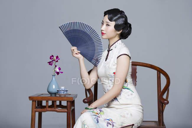 Китаянка в традиционном платье сидит за чайным столом и держит ручной вентилятор — стоковое фото