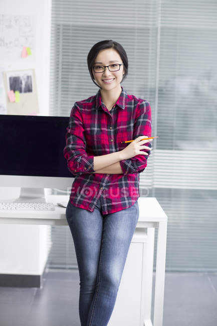 Chinese woman leaning on table with arms folded in office — Stock Photo