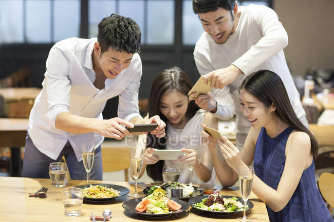 Chinese friends taking photos of dishes in restaurant — Stock Photo