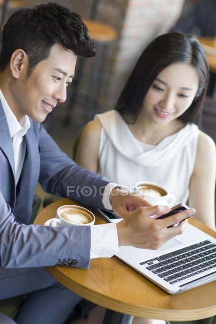 Uomini d'affari cinesi che guardano smartphone in caffè — Foto stock