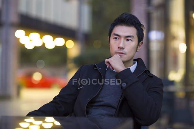 Uomo cinese pensieroso seduto al caffè di strada — Foto stock
