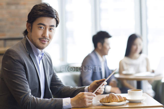 Chinese businessman sitting with digital tablet in cafe — Stock Photo
