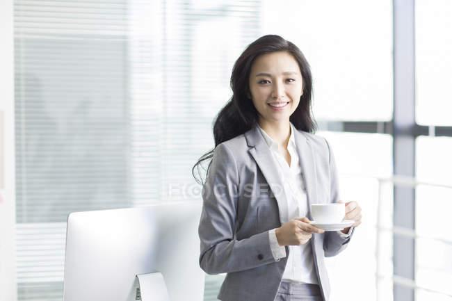 Chinese businesswoman taking coffee break at work — Stock Photo