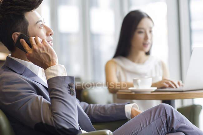 Китайський бізнесмен, розмовляємо по телефону з жінкою, використовуючи ноутбук у фоновому режимі — стокове фото