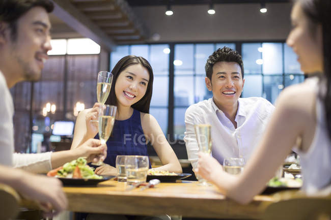 Chinese friends having dinner with champagne — Stock Photo