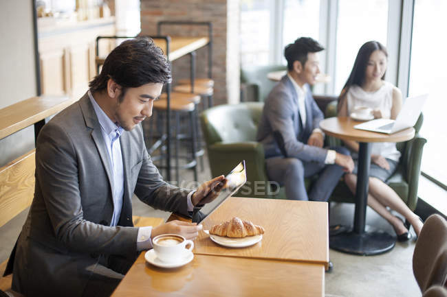 Chinese businessman using digital tablet in cafe — Stock Photo