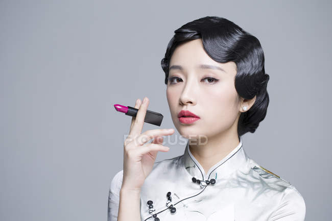 Chinese woman in traditional dress holding lipstick — Stock Photo
