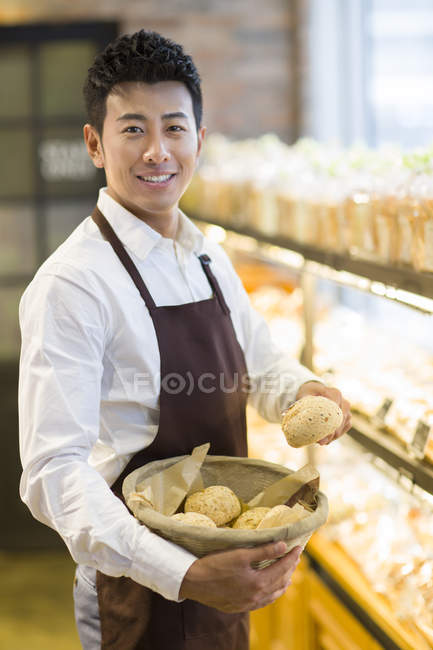 Chinese man holding basket with fresh buns in bakery — Stock Photo