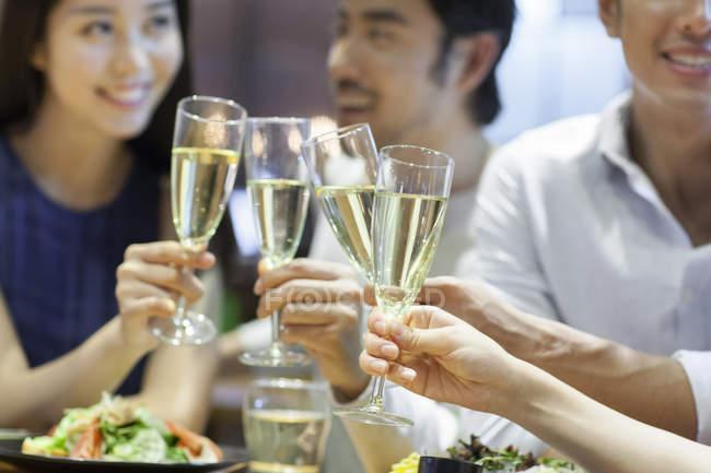 Китайские друзья звонят в стаканы в ресторане — стоковое фото