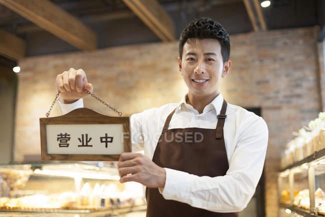 Китайська людина проведення відкритих знак — стокове фото