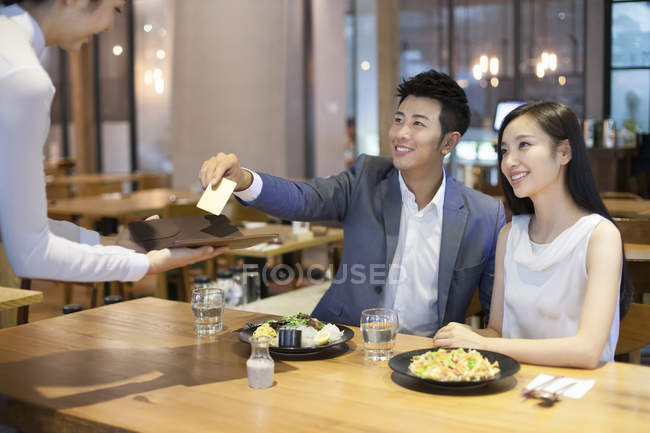 Chinese couple giving waitress credit card in restaurant — Stock Photo