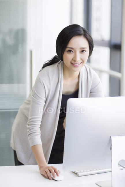 Chinesin steht und benutzt Computer im Büro — Stockfoto