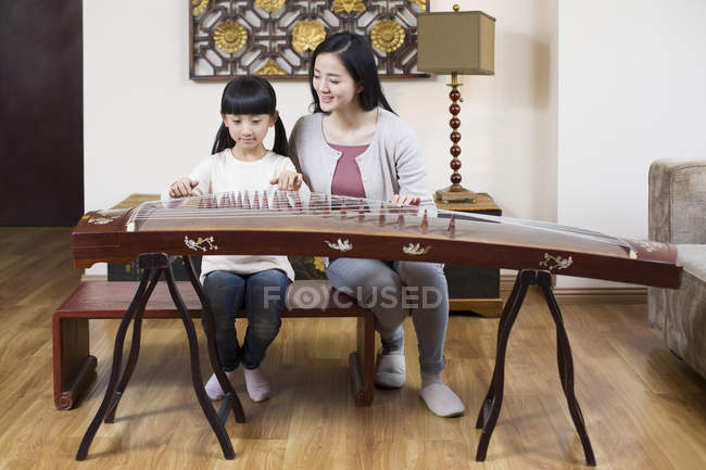 Chinese mother teaching daughter traditional musical instrument zither — Stock Photo