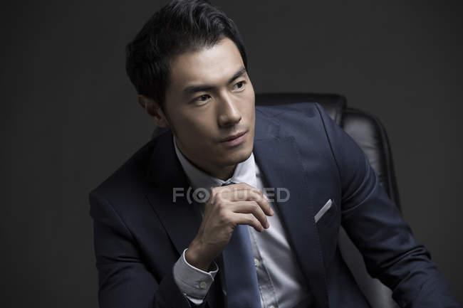 Портрет уверенного китайского бизнесмена, сидящего в кресле — стоковое фото