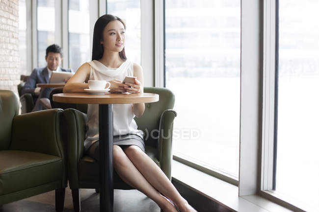 Chinese woman sitting with smartphone and coffee in cafe — Stock Photo