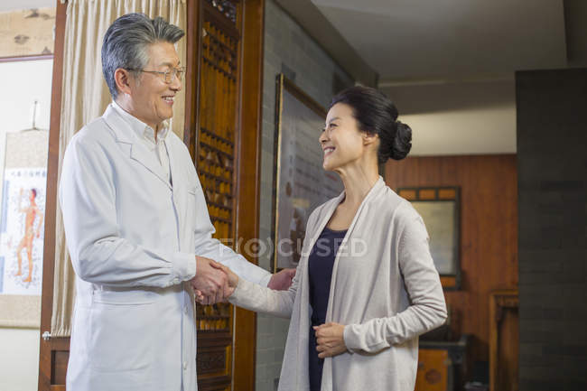 Chinese doctor shaking hands with mature woman — Stock Photo