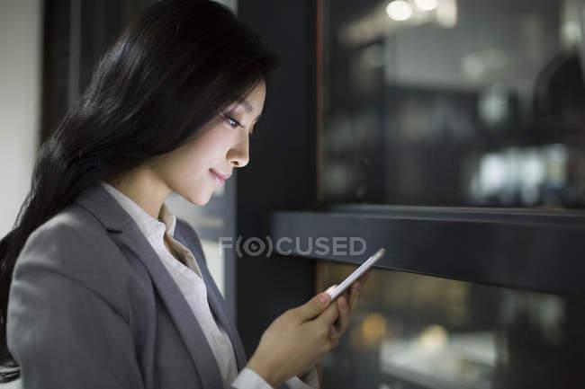Chinesische Geschäftsfrau mit Smartphone durch Bürofenster — Stockfoto