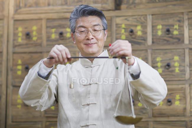 Farmacista cinese che lavora con scala del peso in farmacia — Foto stock