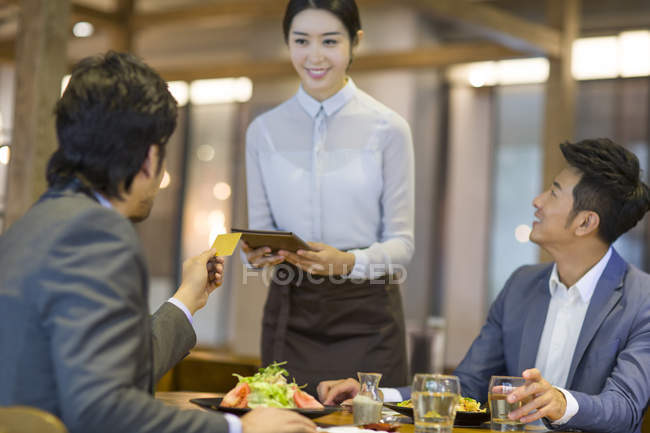 Chinese businessman paying bill by credit card in restaurant — Stock Photo