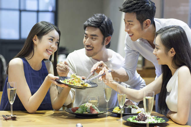 Chinese friends sharing meal in restaurant — Stock Photo