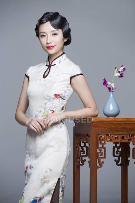 Femme chinoise en habit traditionnel, se penchant sur la table avec des orchidées — Photo de stock