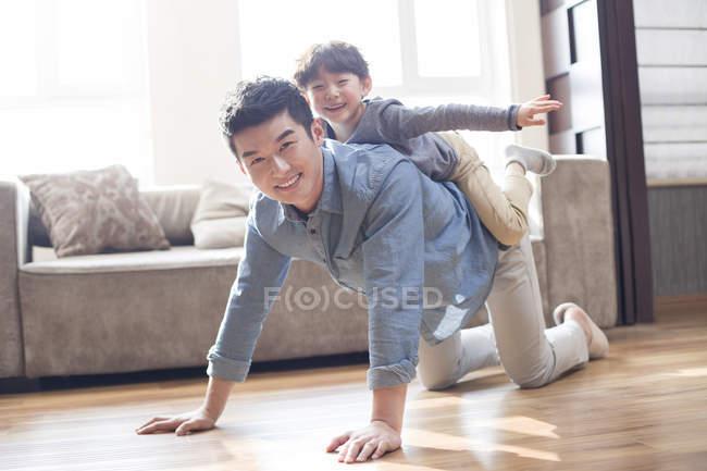 Китайский сын играет и ездит на папе дома — стоковое фото