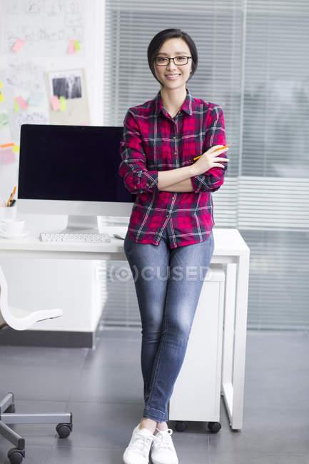 Femme chinoise penchée sur la table avec les bras pliés dans le bureau — Photo de stock