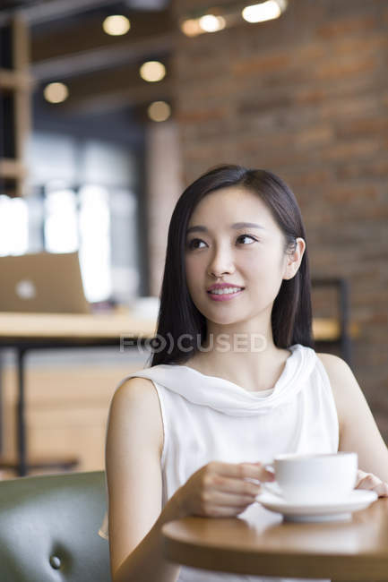Chinese woman sitting with coffee in cafe — Stock Photo