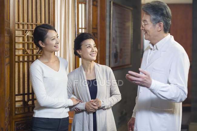 Senior Chinese doctor talking with patients in hallway — Stock Photo