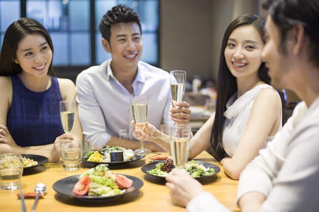 Китайские друзья пьют шампанское за ужином — стоковое фото