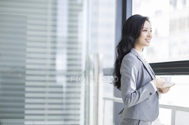 Chinese businesswoman holding coffee and looking through window at office — Stock Photo