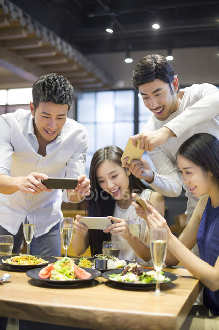Chinese friends taking photos of food in restaurant — Stock Photo