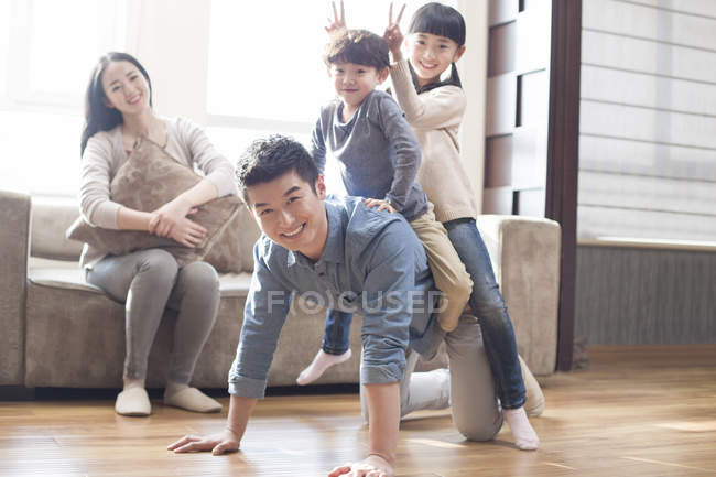 Chinese family having fun in living room — Stock Photo