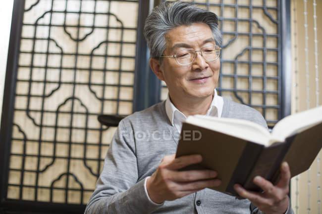 Senior Chinese man reading book — Stock Photo