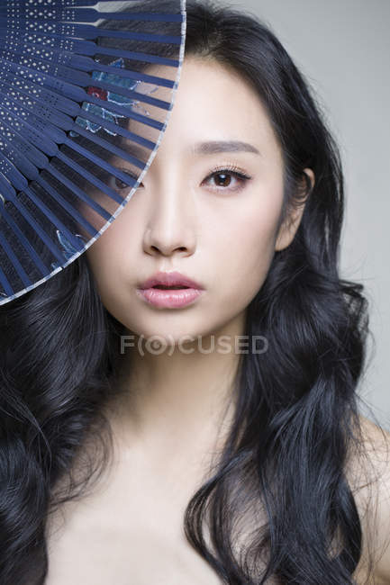 Китайська жінка, що охоплюють обличчя з розбірним вентилятор — стокове фото