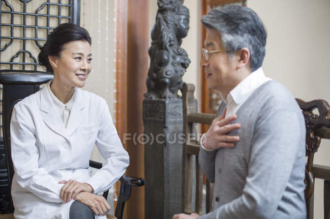 Female Chinese doctor talking with senior patient — Stock Photo