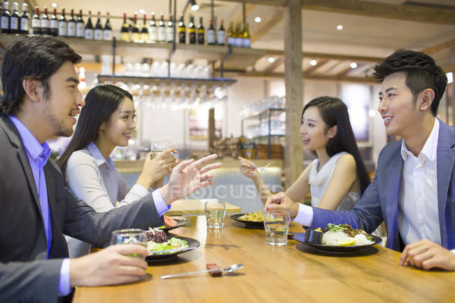 Chinese friends having dinner and talking in restaurant