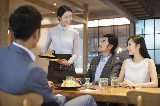 Chinese waitress serving people in restaurant — Stock Photo