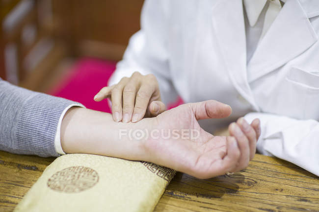 Female doctor taking pulse of patient — Stock Photo