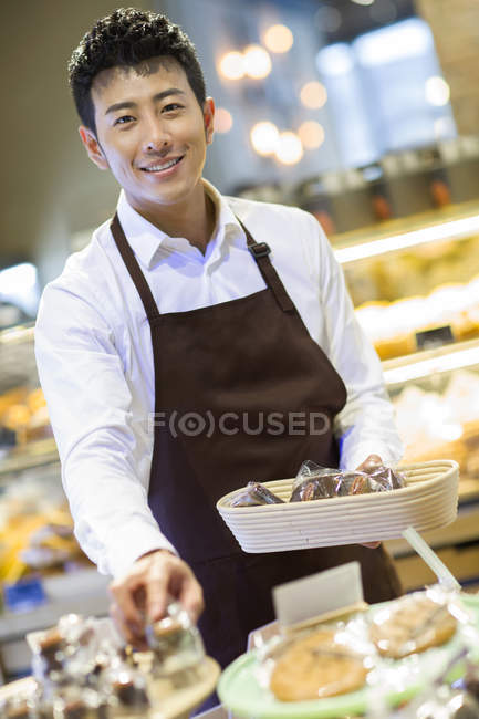 Chinese baker holding basket with fresh bakery products — Stock Photo