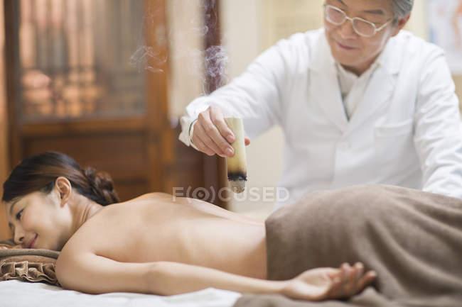 Старший китайский врач, проводящий моксиотерапию для женщин — стоковое фото