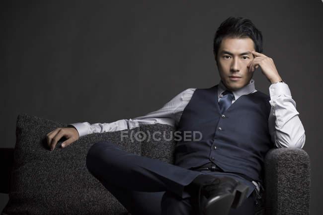 Впевнено китайський бізнесмен, сидячи на дивані, студія постріл — стокове фото