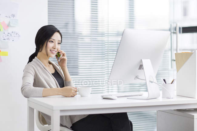 Chinese woman talking on phone at workplace — Stock Photo