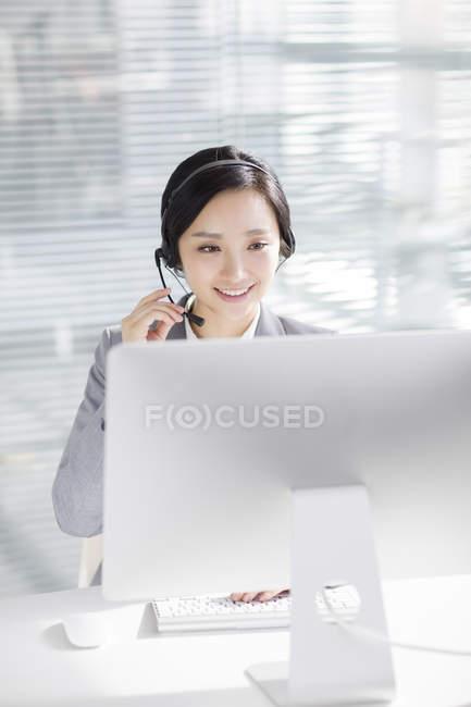 Donna d'affari cinese che utilizza auricolari sul posto di lavoro — Foto stock