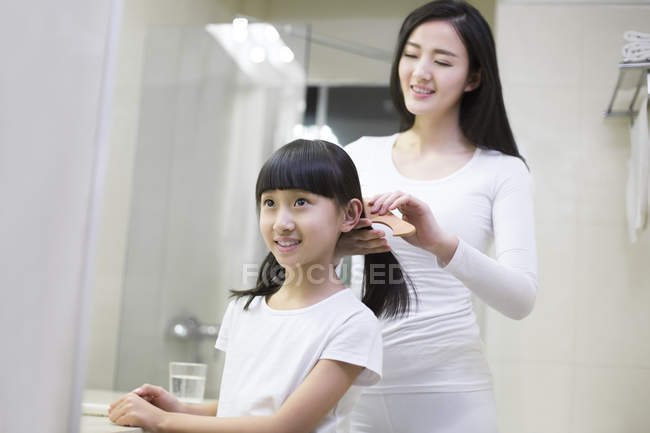 Chinesische Mutter kämmt Tochter Haare im Badezimmer — Stockfoto