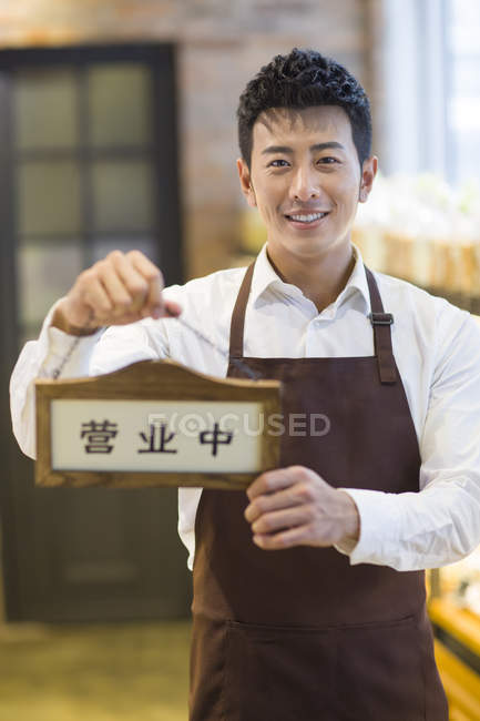 Chinese man holding open sign — Stock Photo