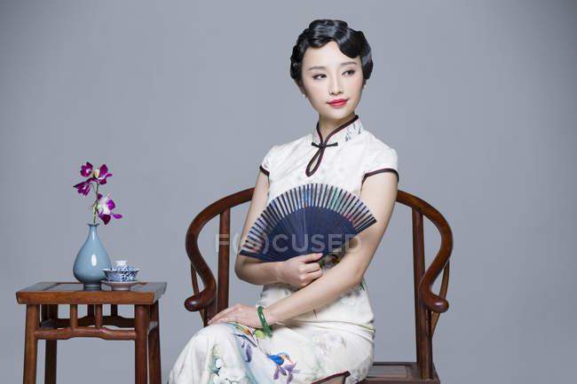 53903ee1d19a Donna cinese in vestito tradizionale seduti al tavolino da tè e palmare fan  della tenuta —
