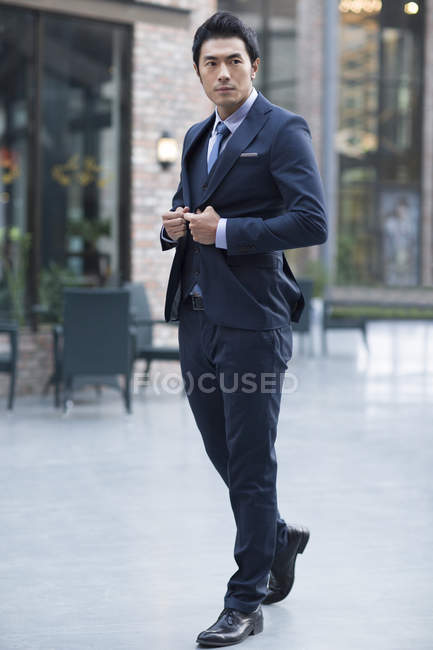 Confident Chinese businessman adjusting suit on street — Stock Photo